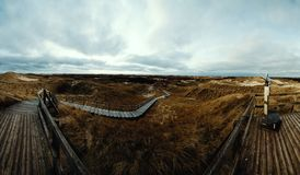 Dramatic Panorama view of a coastal boardwalk, Amrum. Panorama view of a coastal boardwalk crossing vegetated dunes to a viewpoint on a deck on the island of royalty free stock photo