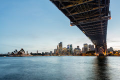 Dramatic panoramic sunset photo Sydney harbor. Dramatic widescreen panoramic image of the city of Sydney at sunset bridge in foreground. Includes the Rocks Royalty Free Stock Photos