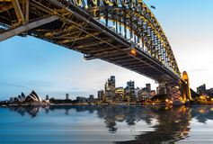 Dramatic panoramic sunset photo Sydney harbor. Dramatic widescreen panoramic image of the city of Sydney at sunset with water replaced by digital reflection Royalty Free Stock Image