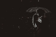 Dramatic photo of a bride and groom in the night rain. royalty free stock photo