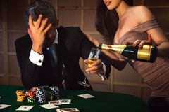 Dramatic photo loser poker man and lady pours him a glass of cha Stock Photo