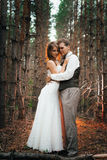 Dramatic picture bride and groom on the background of leaves forest backlight Stock Photo