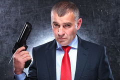 Dramatic picture of an old assassin holding his gun Stock Photography