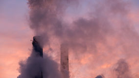 Dramatic pollution sky. Smoke stacks causing dramatic environment pollution on sunset sky royalty free stock image