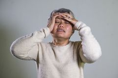 Dramatic portrait of attractive sad and depressed middle aged Asian woman crying helpless suffering depression problem and anxiety stock photo