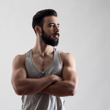 Dramatic portrait of confident strong handsome bearded athlete with crossed arms. Looking away over gray background royalty free stock photo