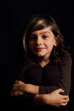 Dramatic portrait of dark haired girl. A dramatic portrait of a smiling dark haired little girl in brown on black. Shallow depth of field Stock Photo