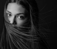 Dramatic portrait of a girl theme: portrait of a beautiful girl with flying hair in the wind against a background in the studio Stock Image