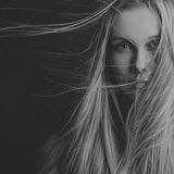 Dramatic portrait of a girl theme: portrait of a beautiful girl with flying hair in the wind against a background in the studio Royalty Free Stock Photos