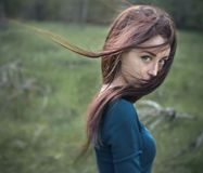 Dramatic portrait of a girl theme: portrait of a beautiful girl with flying hair in the wind in the forest Royalty Free Stock Photography