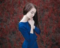 Dramatic portrait of a girl theme: portrait of a beautiful girl in the forest in a blue dress on a background of red grass Royalty Free Stock Photos