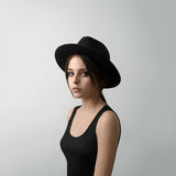 Dramatic portrait of a girl theme: portrait of a beautiful young girl in a black hat and a black shirt on gray background stock photography