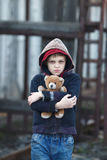 Dramatic portrait of a little homeless boy holding a teddy bear Royalty Free Stock Photos