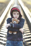 Dramatic portrait of a little homeless boy holding a teddy bear Stock Photo