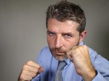 Dramatic portrait of middle aged upset and fierce businessman posing in boxing stance looking furious suffering work stress. Head and shoulders dramatic portrait stock photo