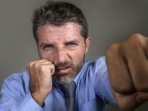 Dramatic portrait of middle aged upset and fierce man boxing throwing punch looking furious suffering work stress fighting for. Head and shoulders dramatic stock photography