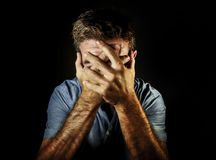 Dramatic portrait of sad and depressed man covering face with hands crying desperate suffering depression and pain having problem stock photo