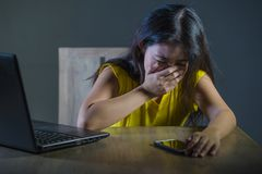 Dramatic portrait scared and stressed Asian Korean teen girl or young woman with laptop computer and mobile phone suffering cyber. Bullying stalked and harassed royalty free stock photo