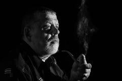 Dramatic portrait of senior smoking tobacco pipe Royalty Free Stock Image