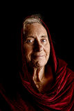 Dramatic portrait of a senior woman wearing a red shawl Stock Photos