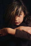 Dramatic portrait of a serious dark haired girl. A dramatic portrait of a somber serious dark haired little girl in brown on black. Blond streaks in her hair Royalty Free Stock Photos