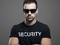 Dramatic portrait of tough macho security guard man with crossed arms Royalty Free Stock Photo