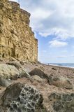 Dramatic portrait view of cliffs at West Bay, Dorset. With rugged rocks in foreground and distant lone figure on beach Royalty Free Stock Photos