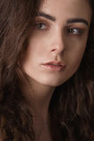 Dramatic portrait of a young beautiful brunette girl with long curly hair in the studio. Royalty Free Stock Images
