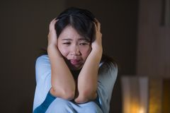 Dramatic portrait of young beautiful and sad Asian Japanese woman crying desperate on bed awake at night suffering depression royalty free stock photography