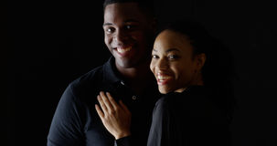 Dramatic portrait of young black woman holding boyfriend and smiling Stock Photo