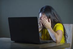 Dramatic portrait of young sad and scared woman covering face with hands stressed and worried looking at laptop computer isolated stock photography