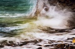 Dramatic powerful squirting water over coast rocks Stock Image