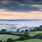 Somerset Levels from Glastonbury Tor England. A dramatic pre-dawn view of the Somerset Levels, from Glastonbury Tor. The mist shrouded landscape and the stormy Royalty Free Stock Photography