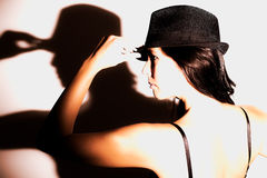 Dramatic profile portrait of a woman in a hat. Dramatic profile portrait of a beautiful serious young woman with a bare back in a fashionable hat holding her royalty free stock photos