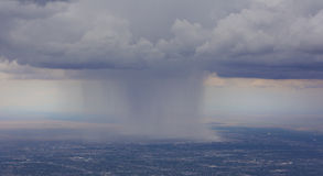 Dramatic rain storm over Albuquerque Airport. Rain pours onto Albuquerque Airport from clouds over the city. View as seen from Sandia Crest Highway on scenic stock photo