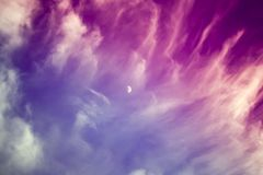 Dramatic red blue purple skies and clouds with the moon in the c. Enter, a surreal landscape Royalty Free Stock Photo