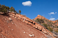 Dramatic red sandstone ridge at Kolob Canyon. With clouds in a blue sky, and winter trees Stock Photos