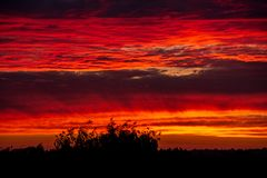Free Dramatic Red Sunset Colors In The Sky Above Trees And Fields Stock Photography - 149371312