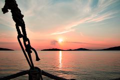Dramatic red sunset reflected in water on deck of a wooden sail boat in croatia stock image