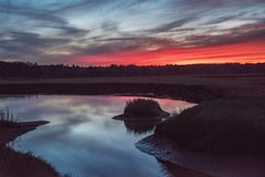 Dramatic red sunset on the river. Dark mystical photo. stock image