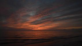 Dramatic red sunset with waves coming to the shore stock video