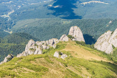 Dramatic rocky peaks set against forested mountain range Royalty Free Stock Photos
