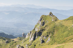 Dramatic rocky peaks set against a misty mountain range Stock Images