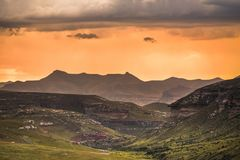 A dramatic scene of golden sunset and storm clouds over the Drakensberg mountains. Surrounding the Amphitheatre, seen from Golden Gate Highlands National Park royalty free stock image