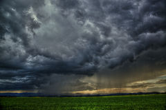 Dramatic scene - meadow with clouds and rain Stock Image