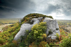 Dramatic scene of a rock with grey clouds Stock Images
