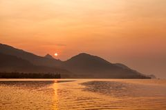 Dramatic scene of sunrise with , sea , mountain , orange sun and boat Royalty Free Stock Photography