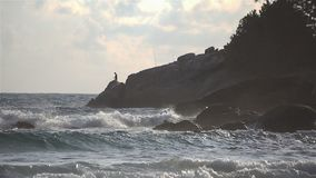 Windy sea wave crashing coast rocks during sunset with fisherman in background stock video