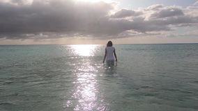 Dramatic scene of a woman entering the sea water at dawn in a backlight with a stormy sky full of clouds. Dramatic scene of a woman entering the sea water at stock video footage