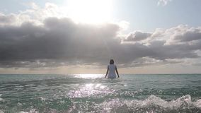 Dramatic scene of a woman entering the sea water at dawn in a backlight with a stormy sky full of clouds. Dramatic scene of a woman entering the sea water at stock video